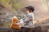 Adorable little boy with his teddy bear friend in the park — Stock Photo