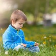 Happy child blowing dandelion outdoors in spring park — Stock Photo #72898909