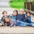 Five adorable kids, dressed in striped shirts, hugging and smili — Stock Photo #72898981
