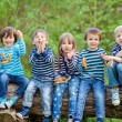 Five adorable kids, dressed in striped shirts, sitting on wooden — Stock Photo #72899151