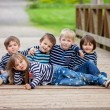 Five adorable kids, dressed in striped shirts, sitting on a brid — Stock Photo #72899163