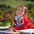 Adorable boy in red sweater, drawing a painting in a book, in th — Stock Photo #72899651