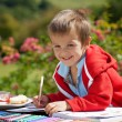 Adorable boy in red sweater, drawing a painting in a book, outdo — Stock Photo #72899667
