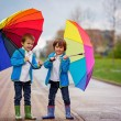 Two adorable little boys, walking in a park on a rainy day, play — Stock Photo #72899969