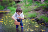 Adorable boy with little basket, full of flowers on a little pon — Stock Photo
