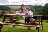 Mother and son, reading a book outdoor, summer day — Zdjęcie stockowe