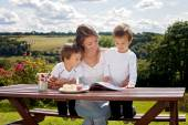 Mother and son, reading a book outdoor, summer day — Stock Photo