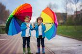 Two adorable little boys, walking in a park on a rainy day, play — Stock Photo