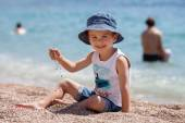 Cute boy, playing with pebbles on the beach — Foto de Stock