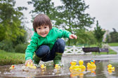 Little boy, jumping in muddy puddles in the park, rubber ducks i — Stock Photo