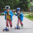 Two cute boys, compete in riding scooters, outdoor in the park — Stock Photo #76260151