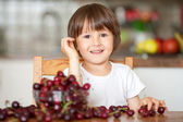 Cute little boy, eating cherries at home in the kitchen, making  — Stock Photo