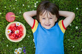 Portrait of sweet little boy, lying on the grass, fresh fruits a — Stock Photo