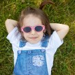 Sweet little girl, laying on the grass, looking at camera, weari — Stock Photo #77105583