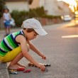Cute little boy, playing with little toy cars on the street on s — Stock Photo #78873664
