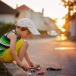 Cute little boy, playing with little toy cars on the street on s — Stock Photo #78873744