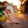 Cute little boy, playing with little toy cars on the street on s — Stock Photo #78874108