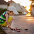 Cute little boy, playing with little toy cars on the street on s — Stock Photo #79224632