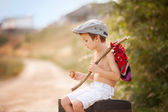 Cute little boy, sitting on a big old suitcase, vintage, holding — Stock Photo