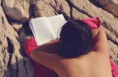 Girl is Reading a Book on Rocky Beach — Stock Photo
