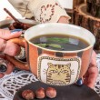 Hands putting tea cup on wooden table with doily — Stock Photo #55909823