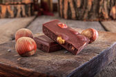 Chocolate with hazelnuts on wooden board — Stock Photo