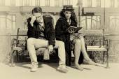 Young couple in quarrel sitting on bench in old town — Stock Photo