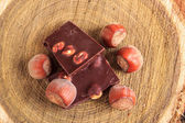 Chocolate and nuts on stump of wood from top view — Photo