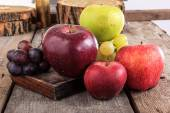 Close up of fresh organic fruits , apples and grapes on the wood — Photo