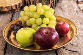 Fresh apples and grapes on golden plate over wooden background — Stock Photo