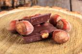 Pieces of chocolate with nuts on stump — Photo
