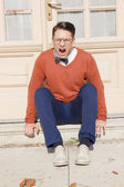 Wütend gut aussehender Mann mit Brille und Pullover auf Schritte im sitzen — Stockfoto