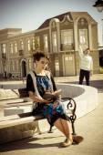 Dívka čtoucí knihu na lavičce ve městě, zatímco muž v poz — Stock fotografie