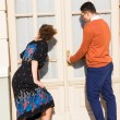 Man with glasses in the orange sweater with woman trying to ope — ストック写真 #57730435