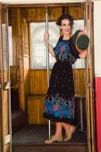 Retro image of a young woman waving in the wagon train or tram — Stock Photo