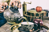 Pouring tea from teapot on old retro wooden table — Stock Photo