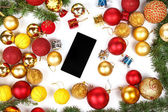Mobile phone with Christmas gifts and finery — Stock Photo