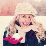 Постер, плакат: Woman in snow holding snow ball on hand for snowballing