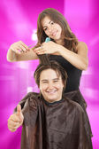 Boy smiling with long hair with thumb up at happy female hairdre — Stockfoto