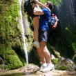 Romantic image, man lifted up woman beside forest waterfall — Foto Stock #76077337