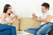 Sceptic young couple cheating each other in card game — Stock Photo