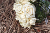 Bridal bouquet of white roses on a faded grass — Stock Photo