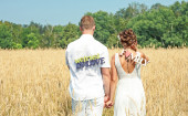 Newly wed couple walking through a grassland — Stock Photo