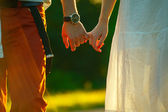 Couple of young people holding hands and walks away into the sun — Foto Stock