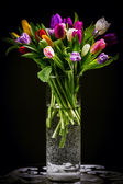 Bouquet of tulips in vase on dark — Stockfoto