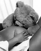 Teddy bear hugs pregnant belly — Stock Photo