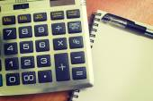 Top view of an office wooden desktop with calculator and pen — Stock Photo