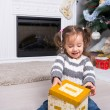 Child under the Christmas tree near the fireplace opens gift. — Stock Photo #58732657
