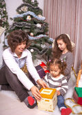 Family with gifts near a Christmas tree. — Stockfoto