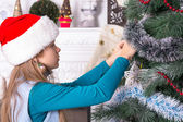 Girl in santa hats decorating the Christmas tree — Stock Photo